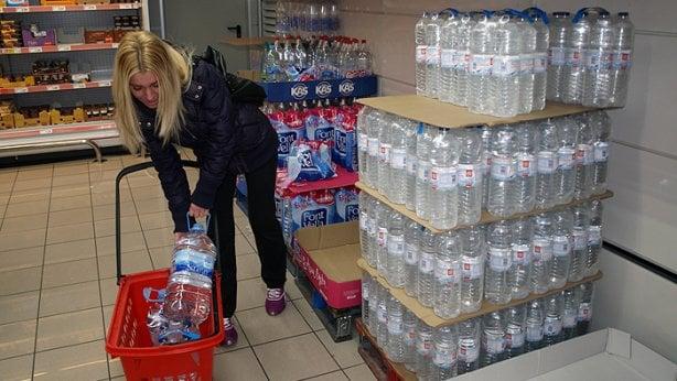 Una mujer introduce en su carro garrafas de agua en un supermercado de Alsasua. (N.M.)