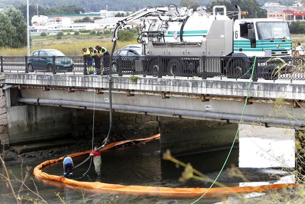 """La asociación """"A Ría non se vende"""" denuncia la destrucción de un hábitat de interés comunitario considerado prioritario, concretamente el amial de Carrasqueira, por las obras de la nueva estación depuradora del Lagares, en Vigo. En la foto de archivo, operarios limpian un vertido contaminante, en septiembre de 2012,  en la desembocadura del río Lagares. EFE / Salvador Sas"""