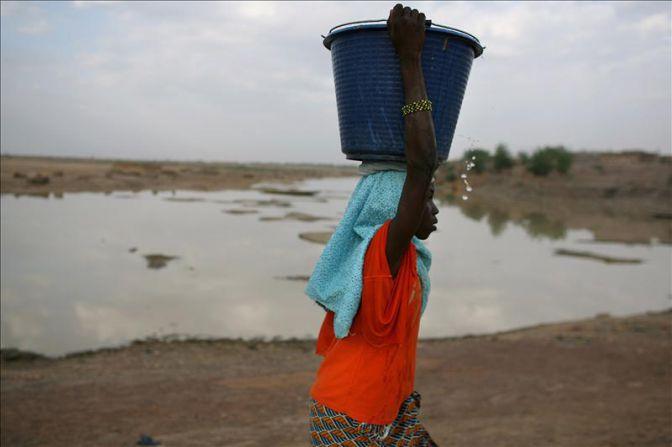 Una niña carga un cubo de agua sobre su cabeza junto al río Bani Transeúntes en la antigua ciudad Djenne (Mali). EFE/Archivo