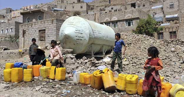 Una mujer y unos niños llenan bidones de agua de una tubería pública en una barriada pobre de Saná (Yemen).EFE/Yahya Arhab
