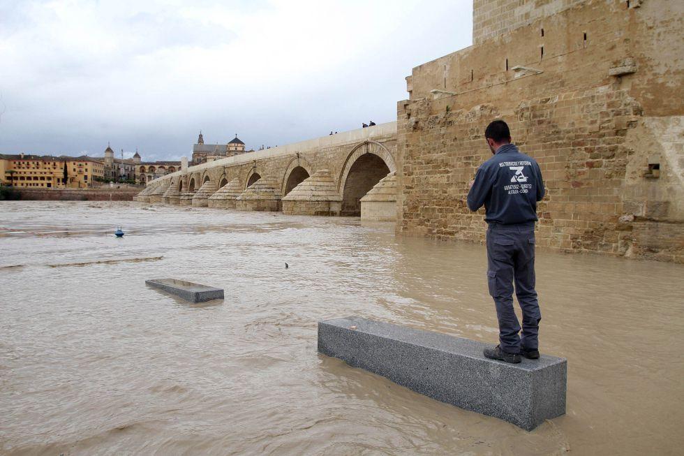 Un vecino observa la crecida del Guadalquivir a su paso por Córdoba./ El País