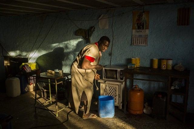 Un hombre recoge un cubo de agua en la cocina improvisada de uno de uno de los cortijos y asentamientos en los que malviven miles de migrantes que trabajan en los invernaderos del municipio almeriense de Níjar. /SANTI PALACIOS /El País