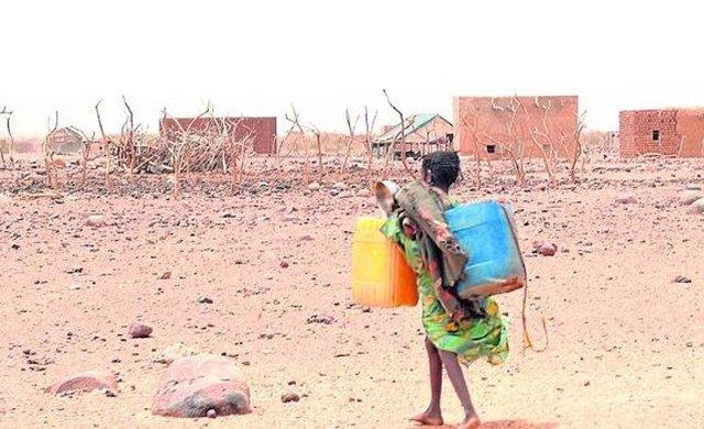 niña carga agua en el Sáhara